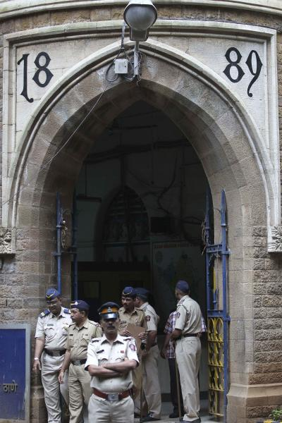 Indian policemen stand guard at a court during a hearing of one of the accused in the gang rape of a photojournalist in Mumbai, India, Sunday, Aug. 25, 2013. Police on Sunday arrested the last of five men wanted in the gang rape of a photojournalist in Mumbai, and said charges would be filed soon in a case that has incensed the public and fueled debate over whether women can be safe in India. (AP Photo/Rafiq Maqbool)