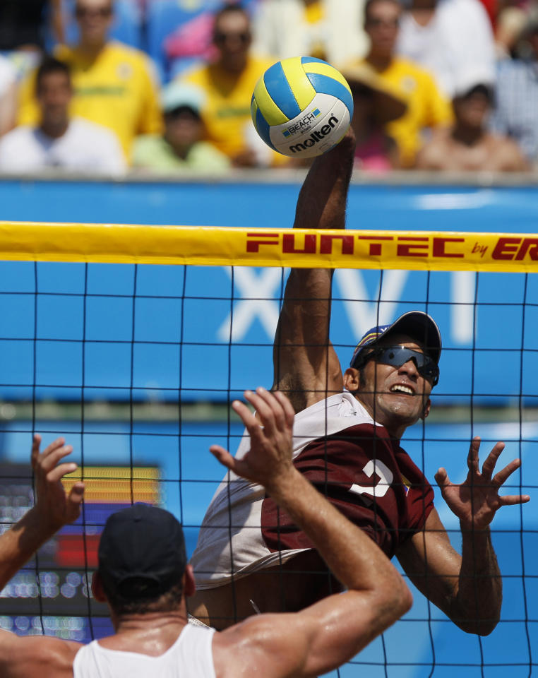 Venezuela's Farid Mussa, right, and Brazil's Alison Cerutti compete during a men's beach volleyball final match at the Pan American Games in Puerto Vallarta, Mexico, Saturday, Oct. 22, 2011. (AP Photo/Ariana Cubillos)