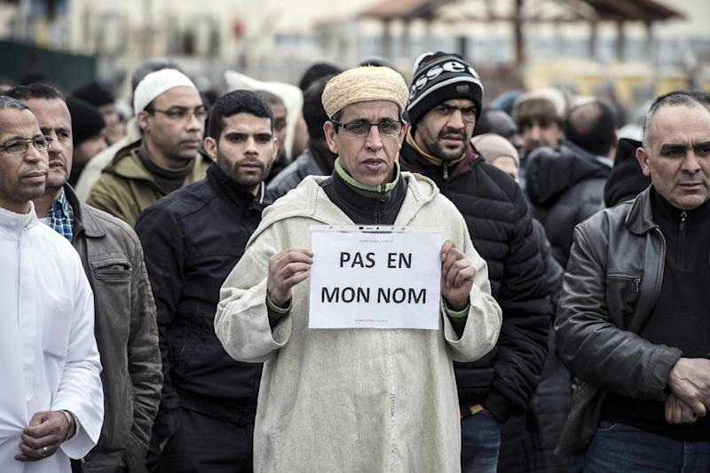 "A Muslim man holds a sign reading ""Not in my name"", during a gathering on January 9, 2015 near the mosque of Saint-Etienne, eastern France, after the attack on the offices of weekly satirical Charlie Hebdo (AFP Photo/Jean-Philippe Ksiazek)"