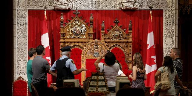 A guard talks to people touring the Senate chamber on Parliament Hill in Ottawa on July 24, 2015.