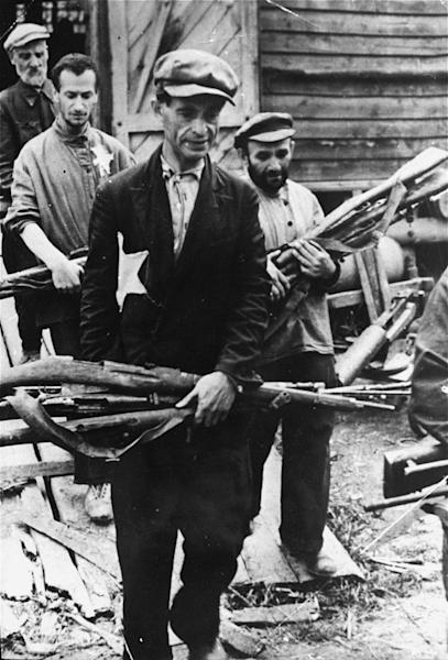 "In this 1941 photo provided by the United States Holocaust Memorial Museum, Jewish men remove looted guns from a barrack in Mogilev, Belarus. Despite all the Holocaust writings, more news is emerging about 1,000 Nazi-run ghettos that left millions of Jews dead. ""Encyclopedia of Camps and Ghettos, 1933-1945, Volume II"" is a global effort that documents every site of organized Nazi atrocities. (AP Photo/United States Holocaust Memorial Museum) MANDATORY CREDIT: UNITED STATES HOLOCAUST MEMORIAL MUSEUM. ONE TIME USE ONLY, NO ARCHIVING"