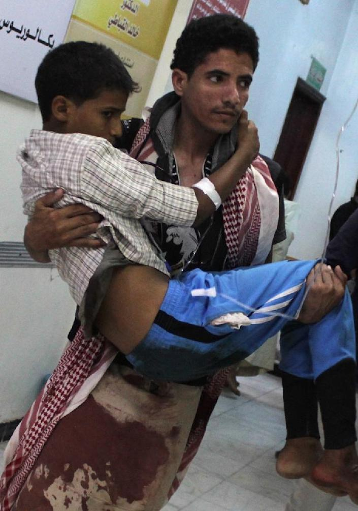 A Yemeni man carries a wounded youth in a hospital in the southern Yemeni city of Taez after he was injured during an exchange of fire between tribal fighters and Shiite Huthi rebels on April 30, 2015 (AFP Photo/Abdel Rahman Abdallah)