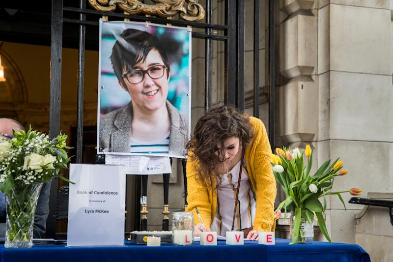 People signing a book of condolence after a vigil at Belfast City Hall in memory of murdered journalist Lyra McKee (Picture: PA)