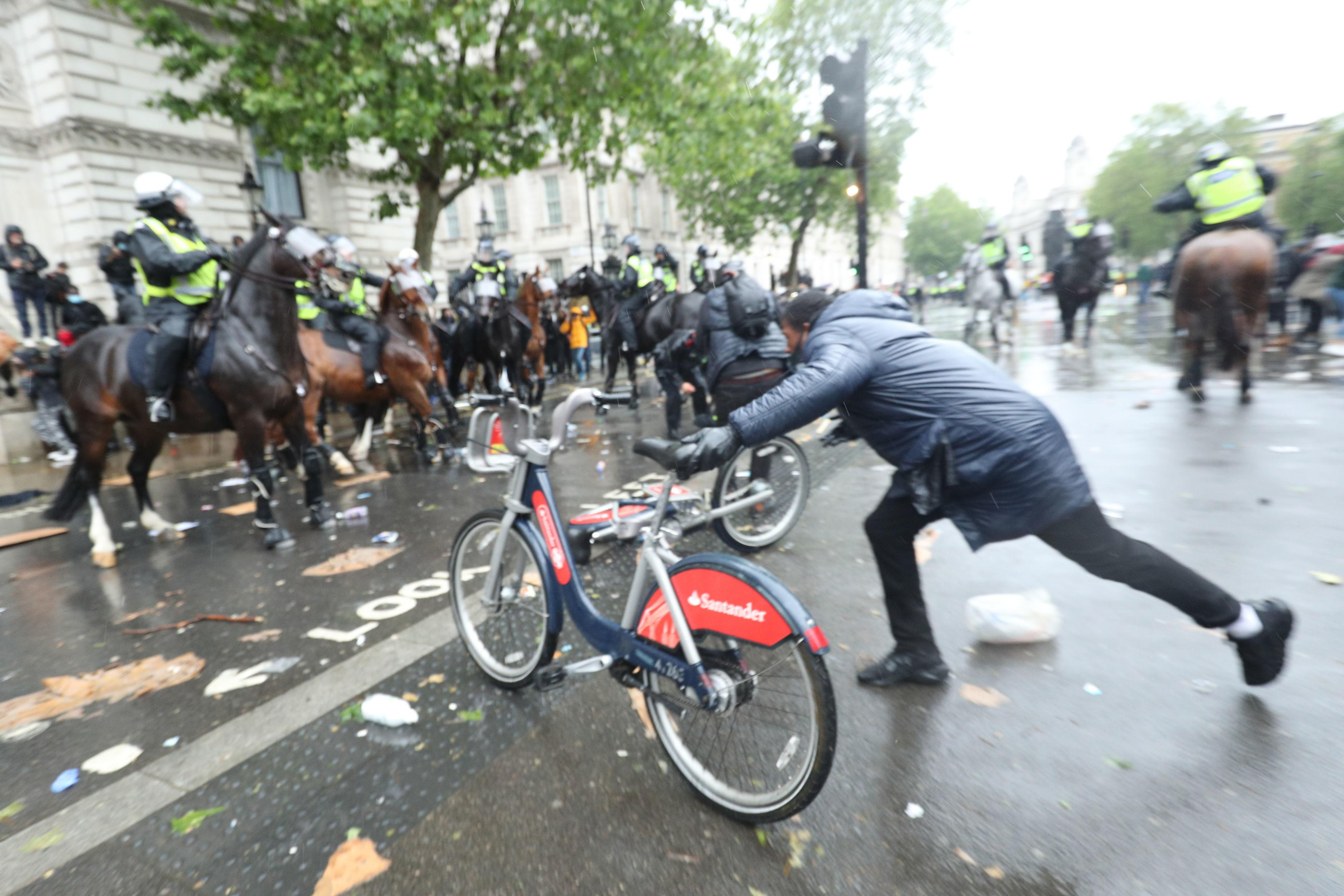 A bicycle is thrown at mounted police Police on horseback in Whitehall following a Black Lives Matter protest rally in Parliament Square, London, in memory of George Floyd who was killed on May 25 while in police custody in the US city of Minneapolis. PA Photo. Picture date: Saturday June 6, 2020. See PA story POLICE Floyd. Photo credit should read: Yui Mok/PA Wire