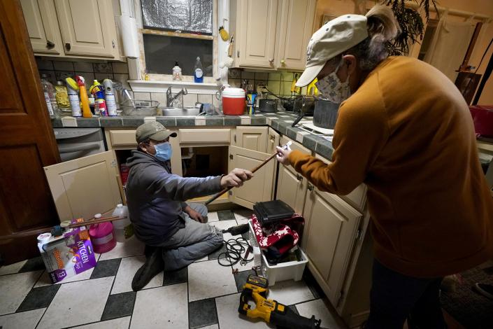 CORRECTS SPELLING OF LAST NAME TO VALERIO, NOT VALERIA - Handyman Roberto Valerio, left, hands homeowner Nora Espinoza the broken pipe after removing it from beneath her kitchen sink on Saturday, Feb. 20, 2021, in Dallas. The pipe broke during freezing temperatures brought by last week's winter weather. (AP Photo/Tony Gutierrez)