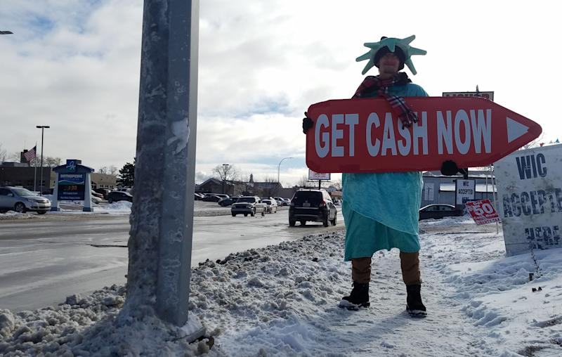 Dressed as Lady Liberty, Brandon Williams holds a sign to Liberty Tax Service outside the Tenth Street office in Port Huron on Monday, Jan. 21, 2019. Williams said he didn't mind working in the day's chilly weather.