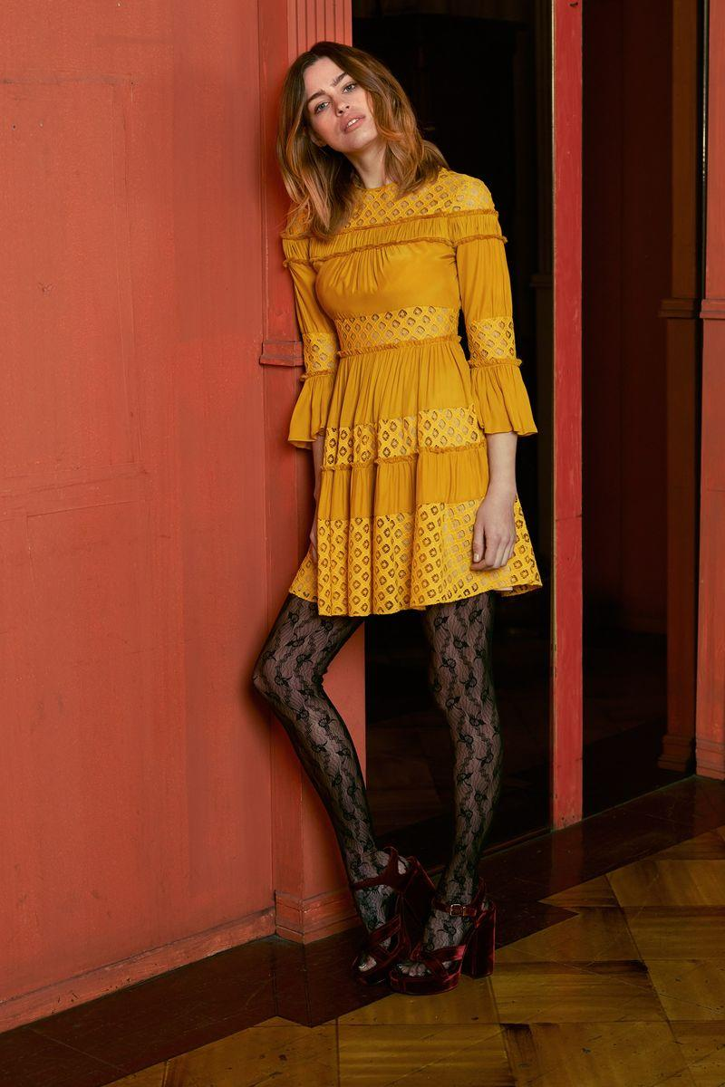 A model wearing a mustard dress and black tights, standing in front of a red wall