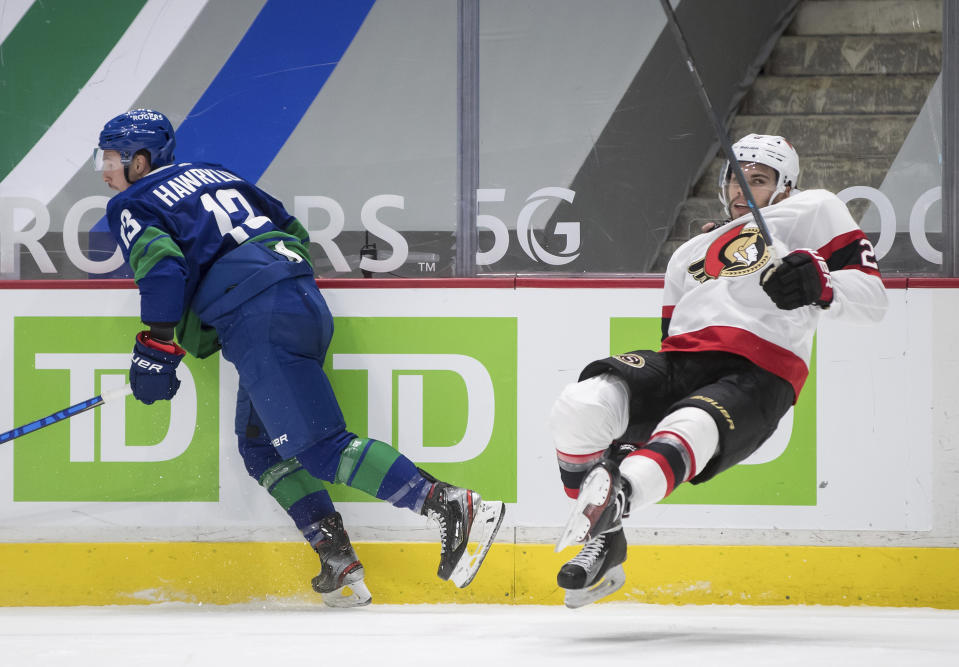 Vancouver Canucks' Jayce Hawryluk, left, sends Ottawa Senators' Artem Zub, of Russia, flying after a collision during the second period of an NHL hockey game in Vancouver, British Columbia, Thursday, April 22, 2021. (Darryl Dyck/The Canadian Press via AP)