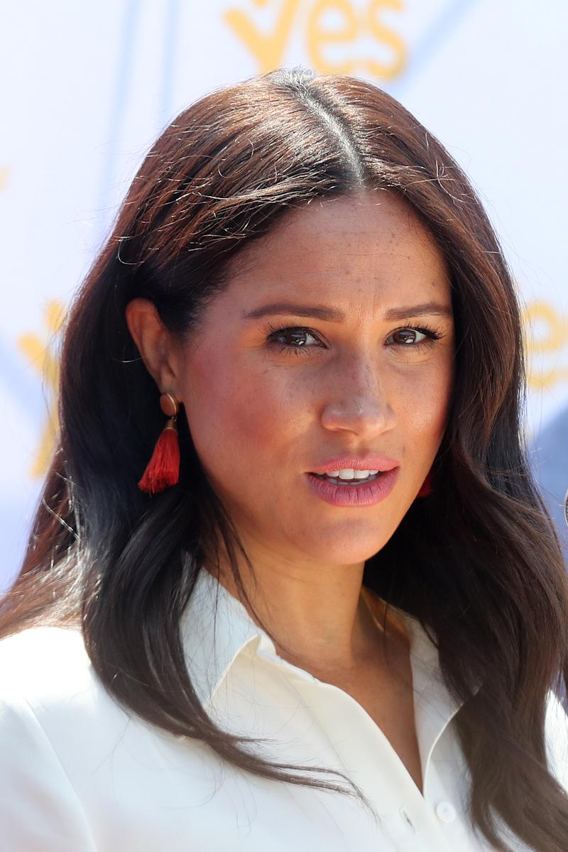 Meghan Markle in white dress and red earrings