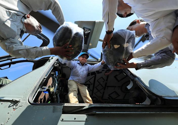 <p>Sanjay Kumar, district magistrate of Allahabad, helps unload relief materials from an Indian Air Force helicopter, in Allahabad, India, Wednesday, Aug. 24, 2016. (AP Photo/Rajesh Kumar Singh)</p>