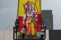 Workers erect a large poster of Hindu Lord Ram on the roof of a service station in Vadodara, Gujarat, on August 5, 2020, to celebrate the groundbreaking ceremony of the Ram Temple in Ayodhya. - India's Prime Minister Narendra Modi will lay the foundation stone for a grand Hindu temple in a highly anticipated ceremony on August 5 at a holy site that was bitterly contested by Muslims, officials said. The Supreme Court ruled in November 2019 that a temple could be built in Ayodhya, where Hindu zealots demolished a 460-year-old mosque in 1992. (Photo by Punit PARANJPE / AFP) (Photo by PUNIT PARANJPE/AFP via Getty Images)