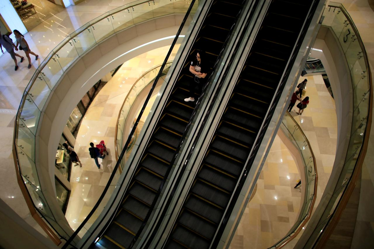 FILE PHOTO: A woman rides down an escalator at a shopping mall in Singapore June 17, 2017.   REUTERS/Thomas White/File Photo                   GLOBAL BUSINESS WEEK AHEAD