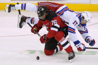 New York Rangers center Kevin Rooney (17) falls over New Jersey Devils defenseman P.K. Subban (76) during the first period of an NHL hockey game, Thursday, March 4, 2021, in Newark, N.J. (AP Photo/Kathy Willens)