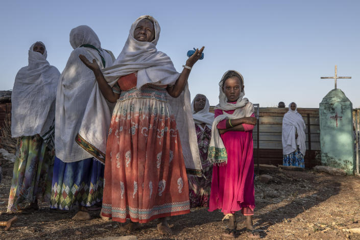 Women who fled the conflict in Ethiopia's Tigray region, prays after Mass at a nearby church in the Umm Rakouba refugee camp in Qadarif, eastern Sudan, Sunday, Nov. 29, 2020. (AP Photo/Nariman El-Mofty)