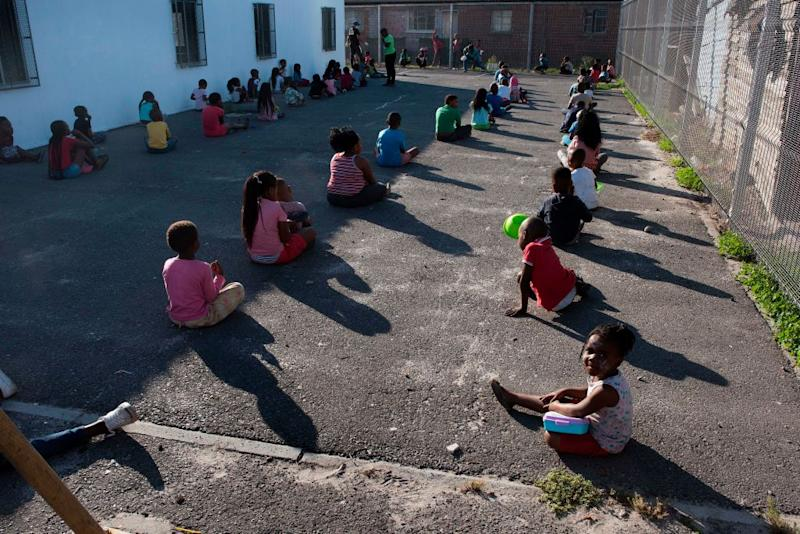 Children social distancing at a nursery near Cape Town wait with bowls to receive soup handed out by the government to prevent the poor from starving amid the pandemic. Source: Getty