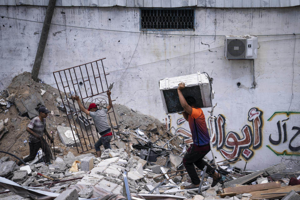 People reclaim valuable materials from a debris pile of a building destroyed by an airstrike prior to a cease-fire reached after an 11-day war between Gaza's Hamas rulers and Israel, in Gaza City, Saturday, May 22, 2021. (AP Photo/John Minchillo)