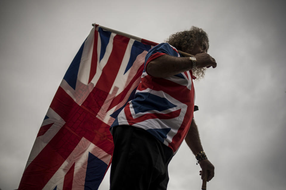 A man carries a Union flag marking the death of Prince Philip, in Gibraltar, Saturday April 10, 2021. Britain's Prince Philip, the irascible and tough-minded husband of Queen Elizabeth II who spent more than seven decades supporting his wife in a role that mostly defined his life, died on Friday. (AP Photo/Javier Fergo)
