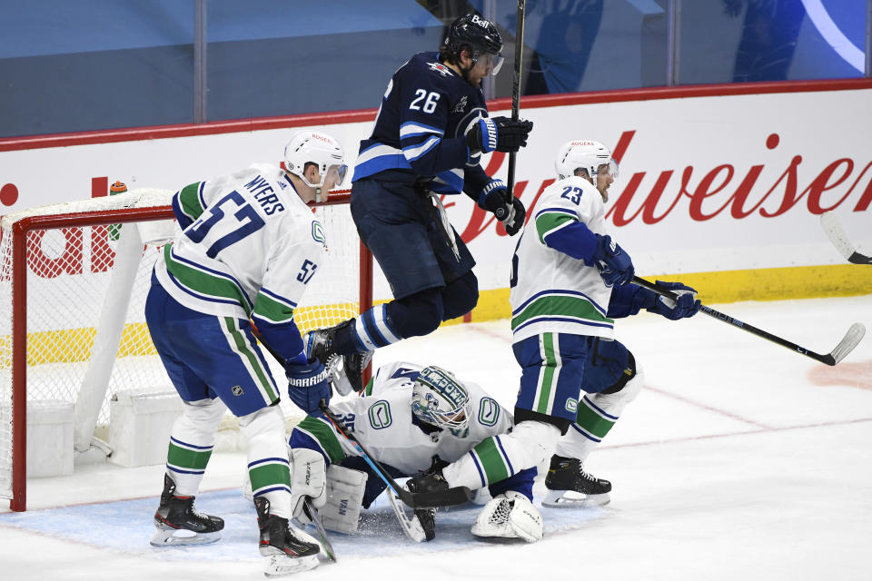Winnipeg Jets' Blake Wheeler (26) jumps over Vancouver Canucks goaltender Thatcher Demko (35) during the third period of an NHL game in Winnipeg, Manitoba, Monday, May 10, 2021. (Fred Greenslade/The Canadian Press via AP)
