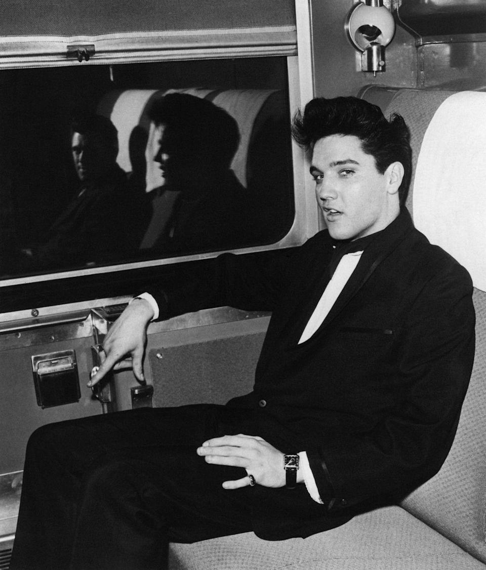 <p>Elvis Presley poses for a photo on a train, circa 1960.</p>