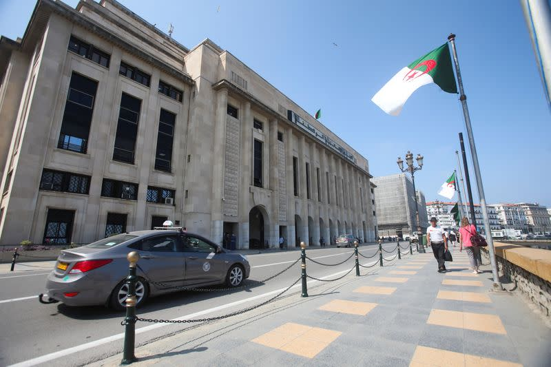 People walk past the building of the lower parliament chamber in Algiers