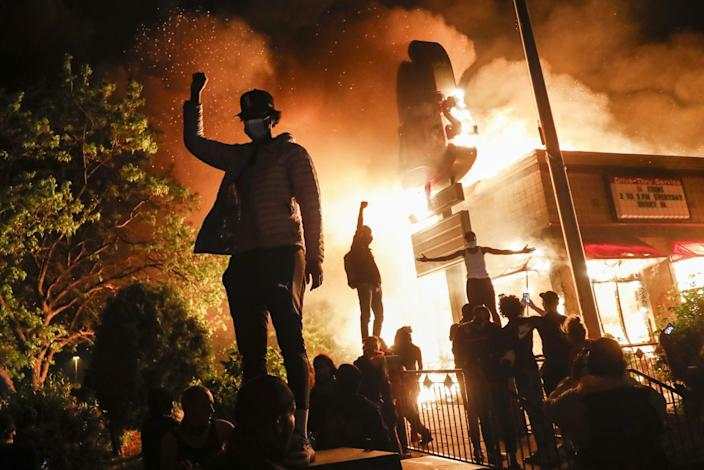 """Protestors demonstrate outside of a burning fast food restaurant in Minneapolis. <span class=""""copyright"""">(John Minchillo / Associated Press)</span>"""