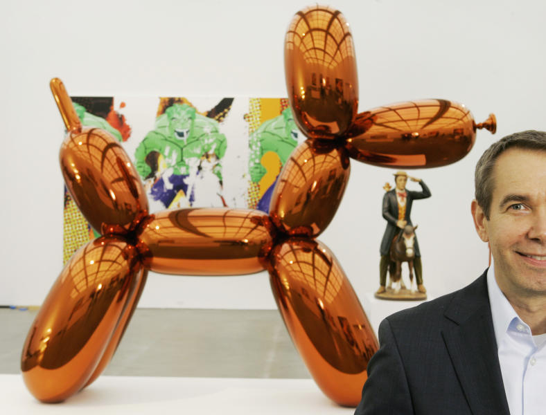 """FILE - In this Thursday, May 29, 2008 file photo, artist Jeff Koons poses beside one of his works, """"Balloon Dog,"""" on display at Chicago's Museum of Contemporary Art. The more than 10-foot-high chromium stainless steel sculpture of a balloon-animal dog has an orange metallic coating and is part of an exhibit of about 60 other sculptures and paintings by Koons. (AP Photo/Charles Rex Arbogast)"""