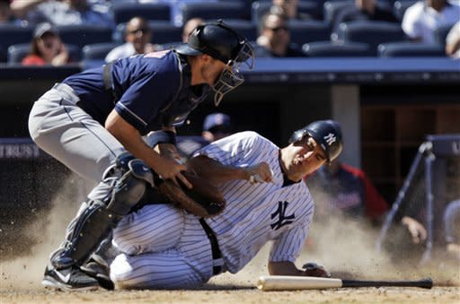 New York Yankees' Mark Teixeira slides into home plate to score as Cleveland Indians catcher Lou Marson (6) attempts to tag him out during the eighth inning of a baseball game Wednesday, June 27, 2012, in New York. Teixeira scored from second on an RBI single by Eric Chavez. The Yankees won the game 5-4. (AP Photo/Frank Franklin II)