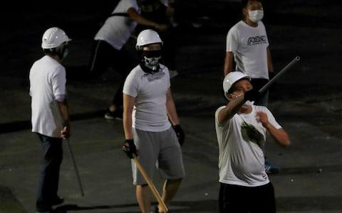 Men in white T-shirts with poles are seen in Yuen Long after they attacked pro-democracy activists at a train station, in Hong Kong - Credit: Reuters