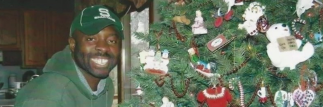 Francis Anwana standing next to a Christmas tree while wearing a green baseball cap and sweatshirt.