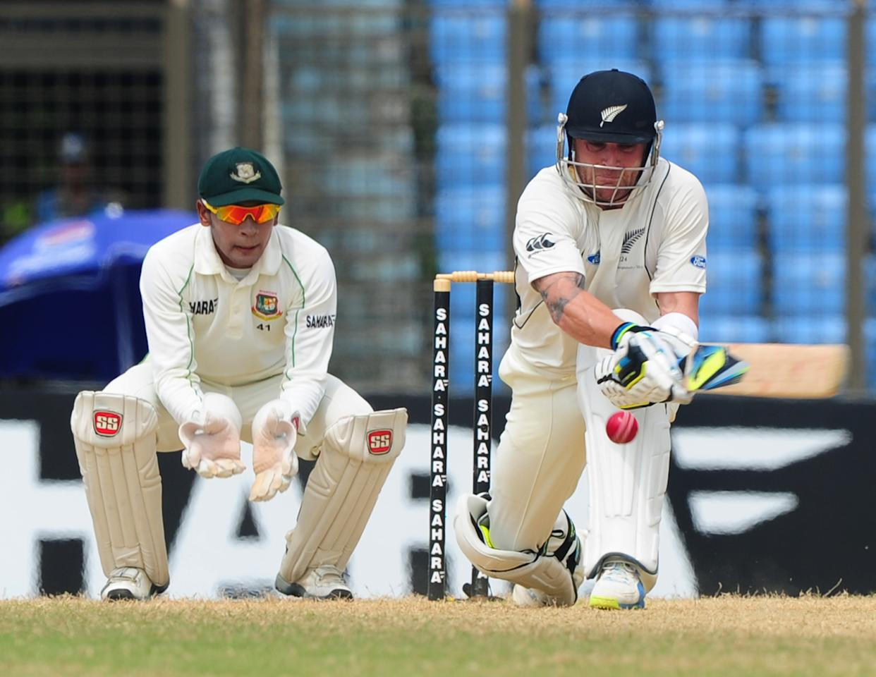 New Zealand captain Brendon McCullum (R) plays a shot as the Bangladesh captain Mushfiqur Rahim looks on during the fifth and final day of the first cricket Test match between Bangladesh and New Zealand at The Zahur Ahmed Chowdhury Stadium in Chittagong on October 13, 2013. AFP PHOTO/Munir uz ZAMAN        (Photo credit should read MUNIR UZ ZAMAN/AFP/Getty Images)
