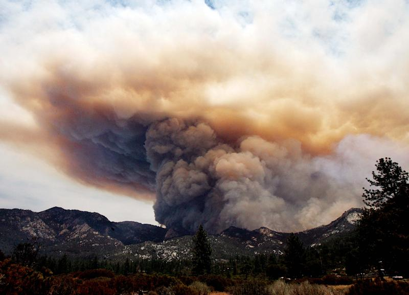 The Mountain Fire near Lake Hemet pours smoke into the sky Tuesday July 16, 2013. The 14,200 acre forest fire near Idyllwild Calif., has caused Idyllwild and adjacent communities east of Highway 243 to issued mandatory evacuations for hundreds of homes Wednesday. (AP Photo/The Press-Enterprise, Frank Bellino)