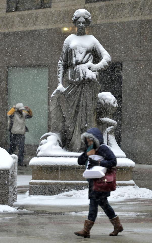 CHICAGO, IL - MARCH 5:  A pedestrian walks by a snow-covered statue in front of the Chicago Board of Trade on March 5, 2013 in Chicago, Illinois. The worst winter storm of the season is expected to dump 7-10 inches of snow on the Chicago area with the worst expected for the evening commute.  (Photo by Brian Kersey/Getty Images)