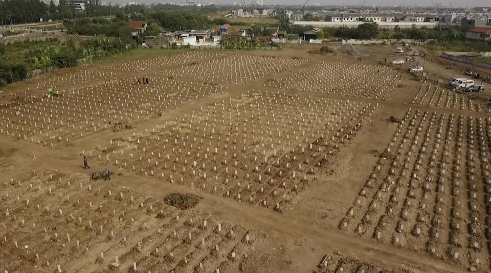In this image from drone video, rows of burial plots are lined up at the Rorotan cemetery, a graveyard built for COVID-19 victims in Jakarta, Indonesia on July 23, 2021. Indonesia surpassed the grim milestone of 100,000 official COVID-19 deaths on Wednesday, Aug. 4, 2021, as the country struggles with its worst pandemic year fueled by the delta variant, with growing concerns that the actual figure could be much higher with people also dying at home. (AP Photo/Andi Jatmiko)