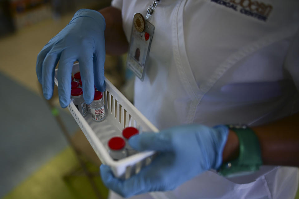 FILE - In this March 10, 2021 file photo, a nurse carries vials of the Moderna COVID-19 vaccine during a mass vaccination campaign, at the Maria Simmons elementary school in Vieques, Puerto Rico. A spike in cases and hospitalizations has put medical experts at odds with the government, which is struggling to protect people's health while also trying to prevent an economic implosion on an island battered by hurricanes, earthquakes and a prolonged financial crisis. (AP Photo/Carlos Giusti, File)