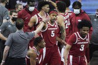 Arkansas guard Moses Moody (5) high-fives a member of the coaching staff during a timeout in the second half of the team's NCAA college basketball game against South Carolina on Tuesday, March 2, 2021, in Columbia, S.C. (AP Photo/Sean Rayford)