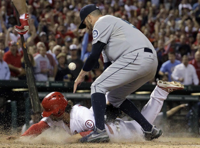 St. Louis Cardinals' Pete Kozma, bottom, scores the game-winning run on a passed ball as Seattle Mariners relief pitcher Oliver Perez covers home during the 10th inning of a baseball game Friday, Sept. 13, 2013, in St. Louis. (AP Photo/Jeff Roberson)