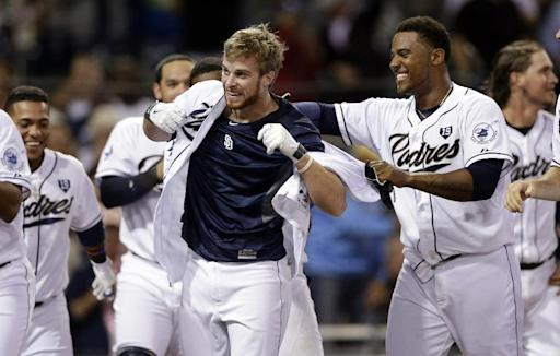 The San Diego Padres' Cory Spangenberg, center, is swarmed by teammates after hitting a walk-off home run against the Arizona Diamondbacks during the ninth inning of a baseball game Tuesday, Sept. 2, 2014, in San Diego. The Padres won 2-1. (AP Photo/Gregory Bull)