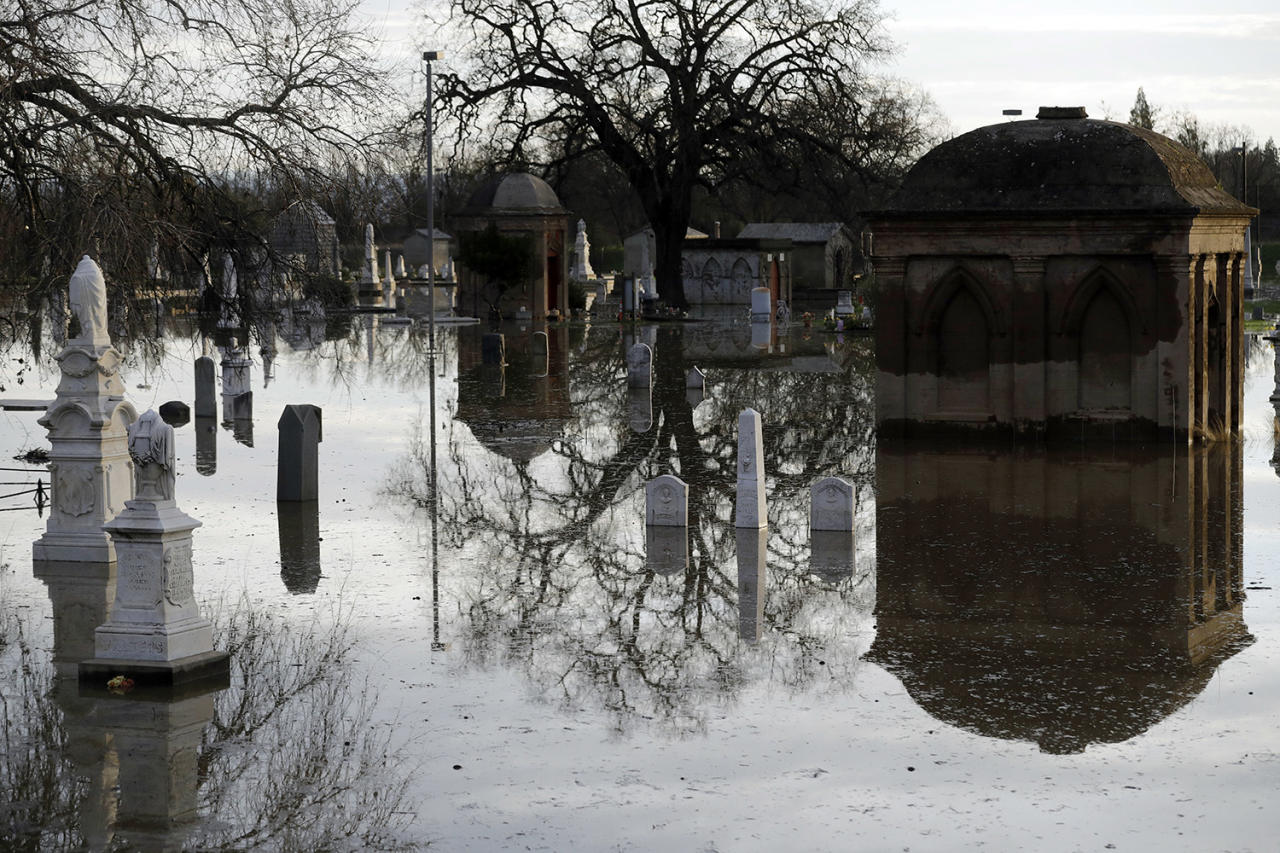 <p>Graves are submerged in floodwaters at a cemetery downstream from a damaged dam, Feb. 15, 2017, in Marysville, Calif. (AP Photo/Marcio Jose Sanchez) </p>