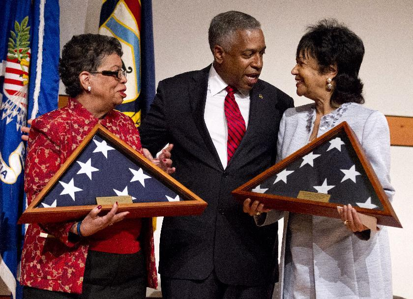 William Henderson Foote's great grand niece Bettye Gardner, left, and great grand daughter Patricia Nolcox, right, is presented with U.S. flags, flown over the Capitol, by Bureau of Alcohol, Tobacco, Firearms and Explosives (ATF) Acting Director B. Todd Jones during a memorial ceremony honoring the first African American post-reconstruction era federal law enforcement officer killed in the line of duty, Monday, May 14, 2012 in Washington. The name of William Henderson Foote, a deputy collector with an ATF legacy agency, the U.S. Department of the Treasury, Bureau of Internal Revenue (BIR), was unveiled on ATF's Memorial Wall during an event commemorating National Police Week. Foote was killed Dec. 29, 1883, in Yazoo City, Miss., almost 130 years ago. (AP Photo/Manuel Balce Ceneta)