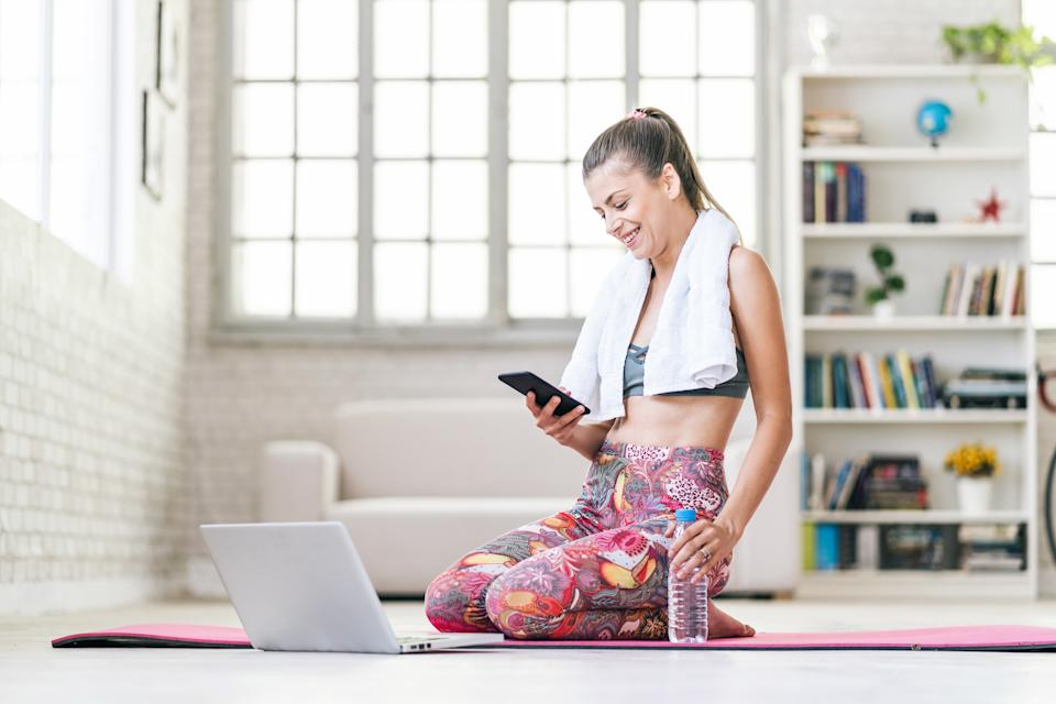 Yoga teacher practicing yoga and making teleconferencing in front of her laptop