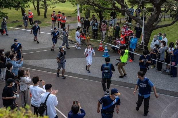 A torchbearer passes along the Olympic torch relay route in Sakata, Japan. As the Olympic torch relay makes its way around the country, much of the original route has been altered or cancelled completely as prefectural authorities act to avoid large gatherings during a fourth wave of COVID-19 cases.