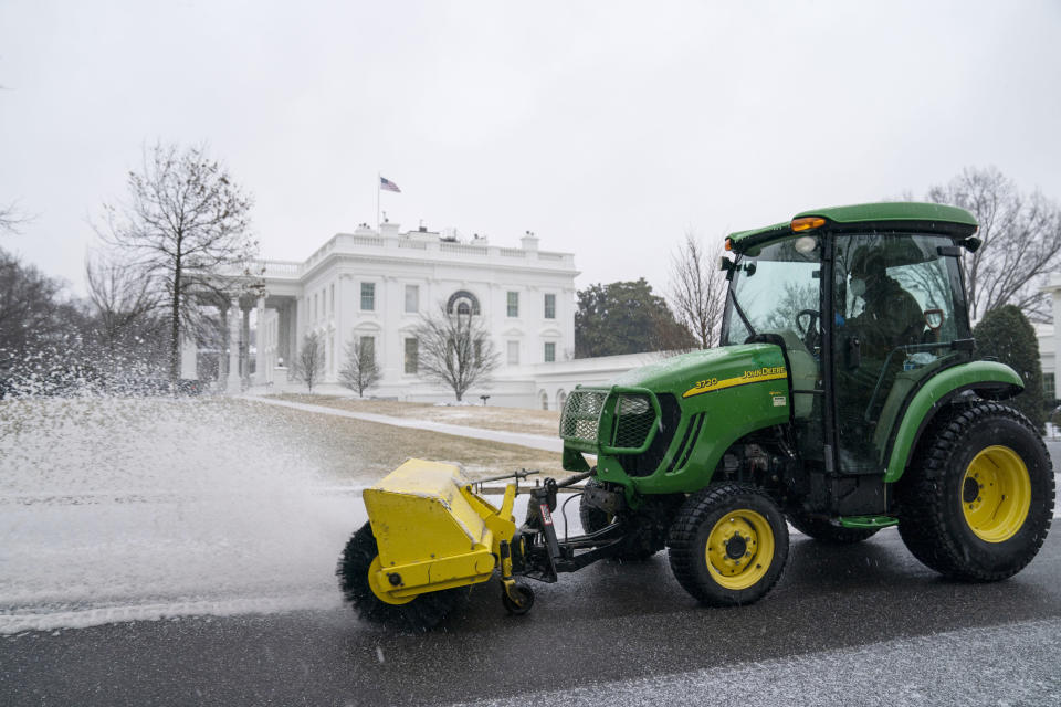 Workers from the National Park Service clear snow and ice at the White House, Thursday, Feb. 18, 2021, in Washington. (AP Photo/Evan Vucci)