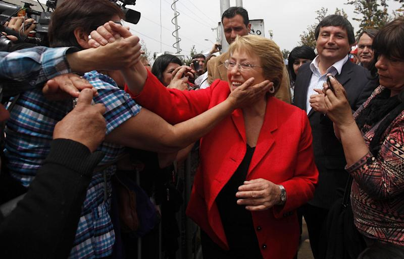 Chile's former President Michelle Bachelet shakes hands with supporters one day after general elections in Santiago, Chile, Monday, Nov. 18, 2013. Bachelet, Chile's first female president from 2006 to 2010, is widely expected to win a Dec. 15 runoff over her childhood friend, Evelyn Matthei. (AP Photo/Luis Hidalgo)