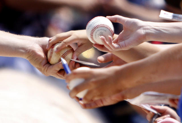Fans try to get autographs before a baseball game between the Atlanta Braves and the Boston Red Sox on Monday, May 26, 2014, in Atlanta, Ga. (AP Photo/Butch Dill)