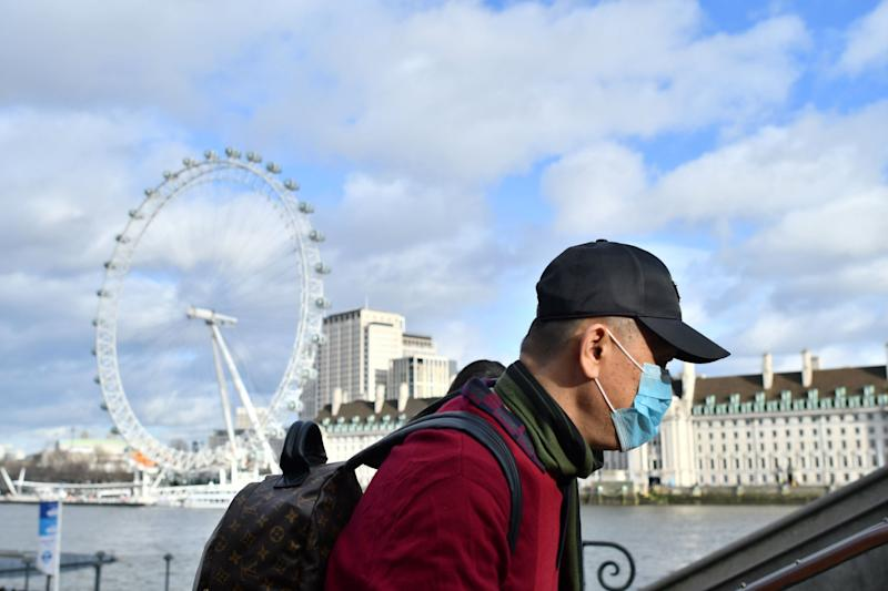 A man is seen wearing a mask while walking along the Thames (AFP via Getty Images)