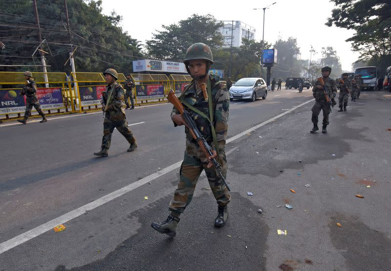 Soldiers patrol a street following protests after India's parliament passed Citizenship Amendment Bill, in Guwahati