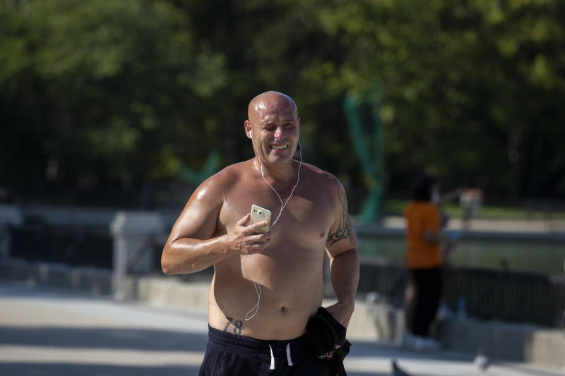 A man jogs during a hot day of summer at the Retiro park in Madrid, Spain, Wednesday, July 29, 2020. The first heat wave of the summer, which will arrive this Thursday and will last at least until next Saturday will leave temperatures over 34 Celsius (104 Fahrenheit). (AP Photo/Manu Fernandez)