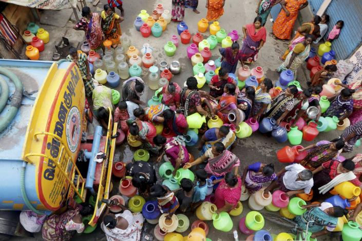 Indiand stand in queues to fill vessels filled with drinking water from a water tanker in Chennai, capital of the southern Indian state of Tamil Nadu, Wednesday, June 19, 2019. Millions of people are turning to water tank trucks in the state as house and hotel taps run dry in an acute water shortage caused by drying lakes and depleted groundwater. Some private companies have asked employees to work from home and several restaurants are closing early and even considering stopping lunch meals if the water scarcity aggravates. (AP Photo/R. Parthibhan)