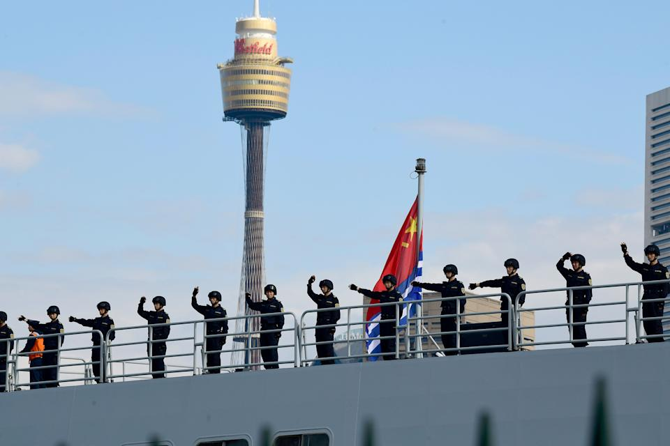 Chinese Navy personnel are seen waving onboard a Navel ship after it arrives at Garden Island.