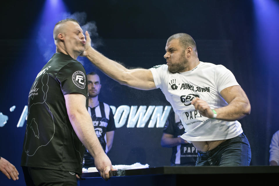"""In this March 7, 2020, handout photo provided by Punch Down, Przemyslay """"Sutek"""" Sutkowski, left, and Lukasz """"Dunaj"""" Dunajko compete in the Punch Down slap fight event in Poznan, Poland. Slap fighting, the art of striking another fighter with an open hand for sport, is the latest head-turning spectacular. (Wojciech Rogowski/PunchDown via AP)"""